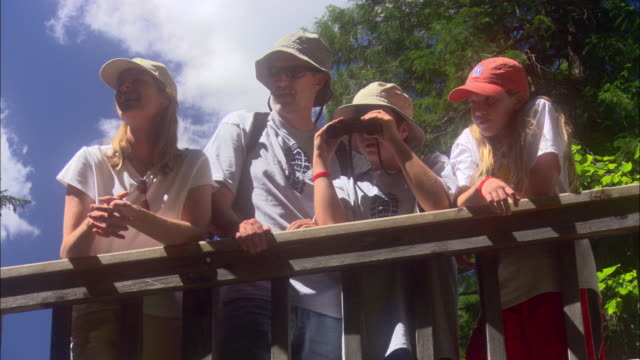 Parents and their two children stand at a railing to observe their surroundings at Glacier National Park.