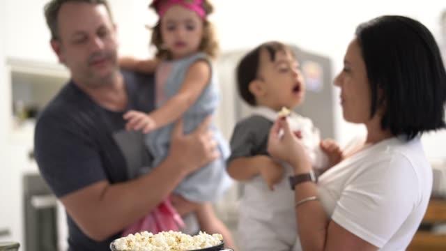 vídeos de stock, filmes e b-roll de pais e irmão gêmeo (filho e filha da síndrome de down) que comem a pipoca em casa - etnia caucasiana
