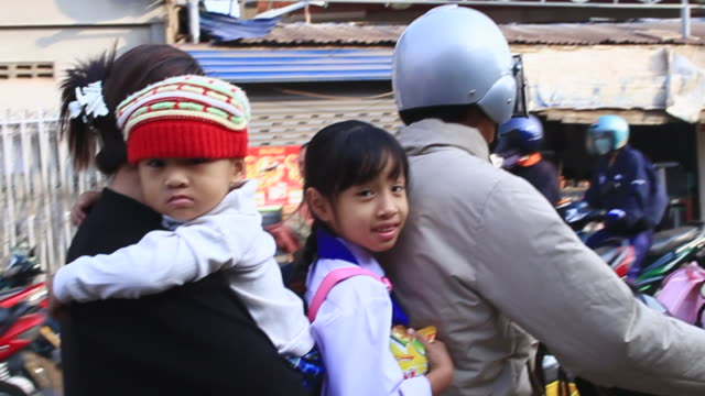 ms pov slo mo parents andchildren on motorbike passing through street / vientiane, laos - four people stock videos & royalty-free footage