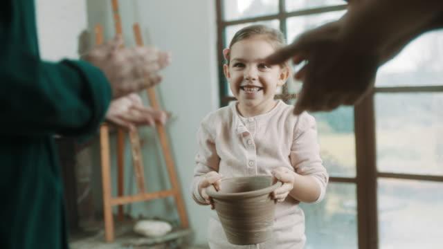 vídeos de stock, filmes e b-roll de pais aplaudindo a sua filha que fez vaso de flor - ocupação artística