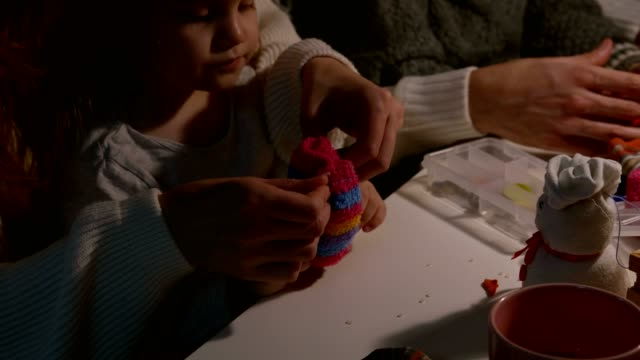 parents assisting their two kids finish their craft snowmen made out of sock - sock stock videos & royalty-free footage