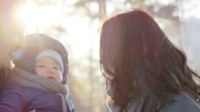 vídeos de stock, filmes e b-roll de parents bonding with baby at snowy day - jaqueta