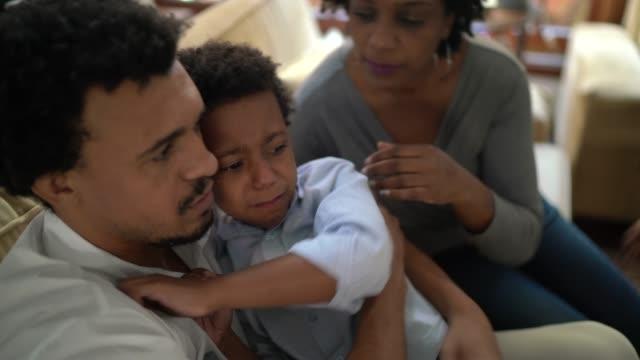vidéos et rushes de parents consolant le fils après qu'il ait fait mal à la maison - enfant d'âge scolaire