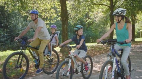 stockvideo's en b-roll-footage met ts ouders fietsen in het zonnige park met één zoon paardrijden zijn fiets en de andere zitten in de zetel op zijn papa's fiets - cycling