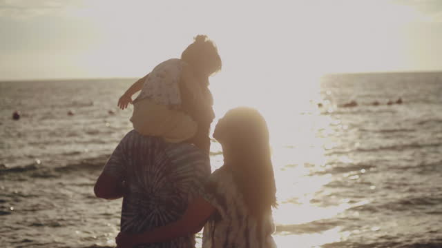 parents enjoying their daughters happily on the beach. - two parents stock videos & royalty-free footage