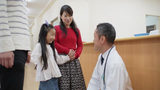 親は子供の病院での予定に小さな女の子を護衛します - 小児科医点の映像素材/bロール