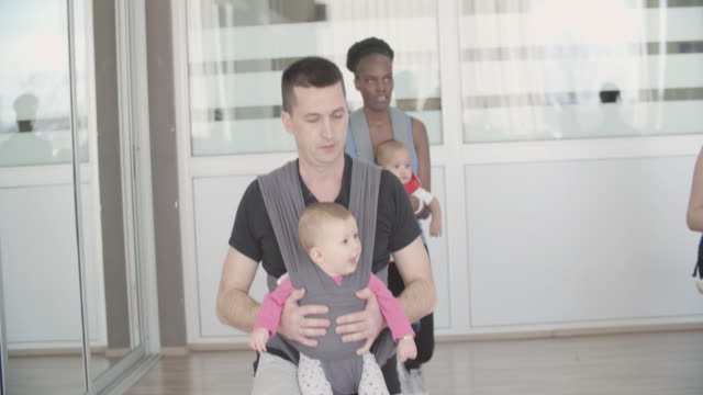 4k: parents exercising with their babies in a gym - baby carrier stock videos & royalty-free footage