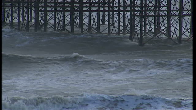 parents face lottery for school places; rough sea waves rolling beneath pier general view brighton pier on winter's day brighton seafront with road... - ブライトン パレスピア点の映像素材/bロール