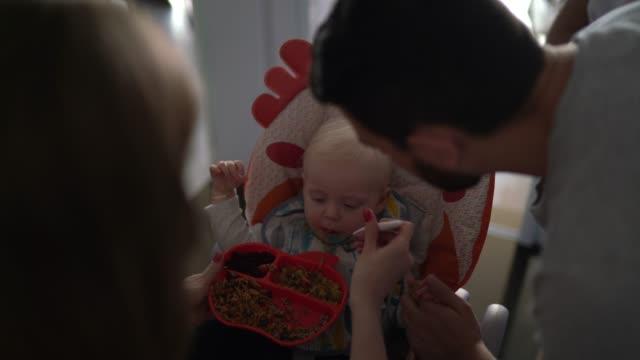 vídeos de stock, filmes e b-roll de pais alimentam criança na cozinha - comendo