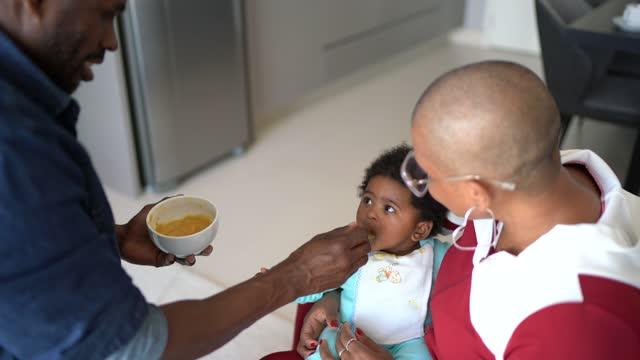 eltern füttern babysohn zu hause - reinheit stock-videos und b-roll-filmmaterial