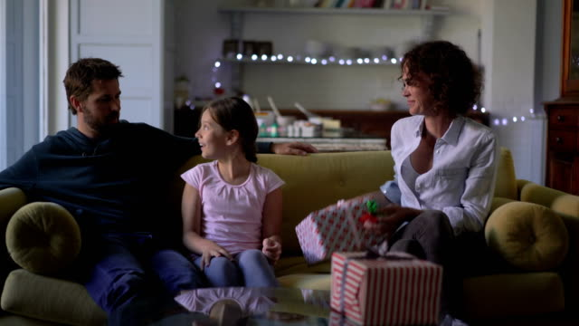 Parents giving christmas gift to girl at home