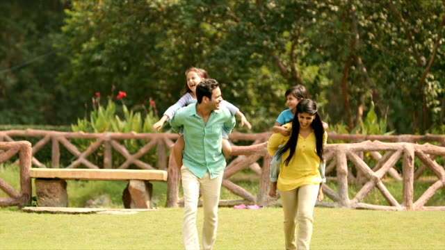vídeos de stock e filmes b-roll de ms parents giving piggyback ride to their children in backyard / delhi, india - família jovem