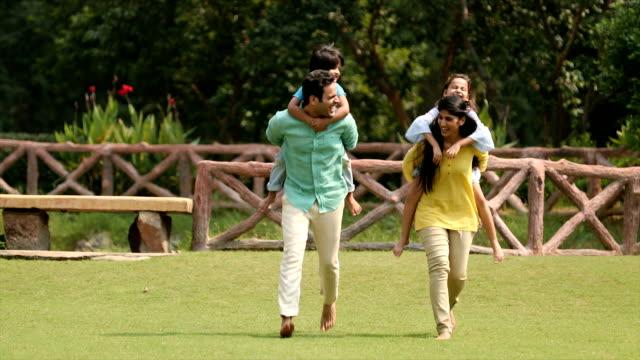 ms parents giving piggyback ride to their children in backyard / delhi, india - 若い家族点の映像素材/bロール