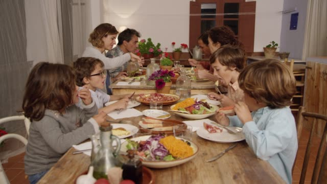 parents having food with children at dining table - dining table stock videos & royalty-free footage