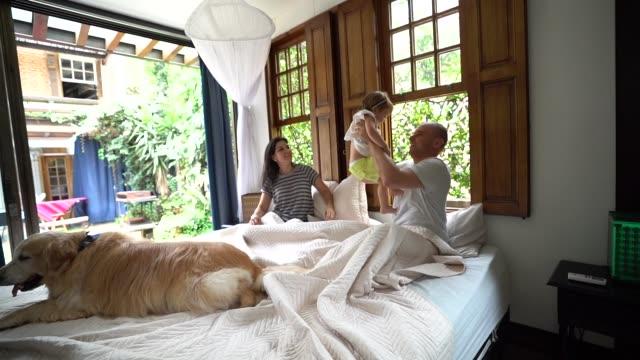 vídeos de stock e filmes b-roll de parents having fun with a cute daughter at bed - domestic room