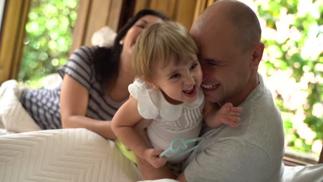 vídeos de stock, filmes e b-roll de pais se divertindo com uma filha na cama - bebês meninas