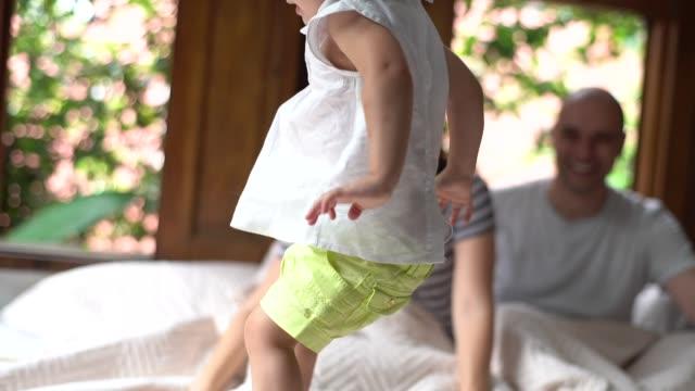 vídeos de stock, filmes e b-roll de pais se divertindo com uma filha na cama - cama