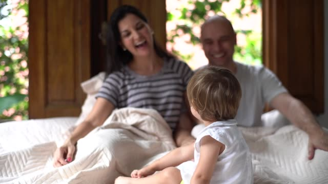 parents having fun with a cute daughter at bed - 35 39 years stock videos & royalty-free footage