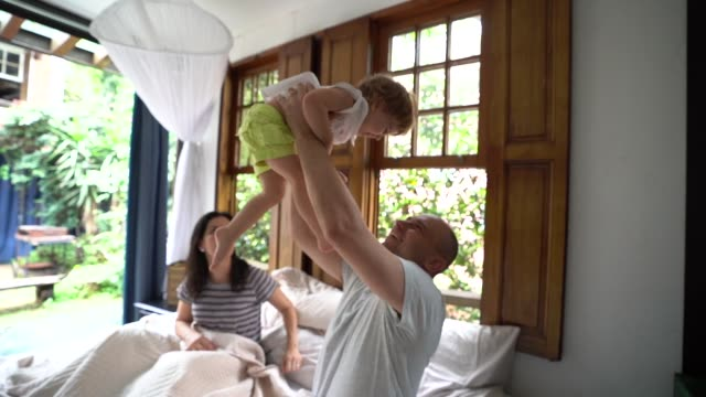 vídeos de stock, filmes e b-roll de pais se divertindo com uma filha na cama - etnia caucasiana