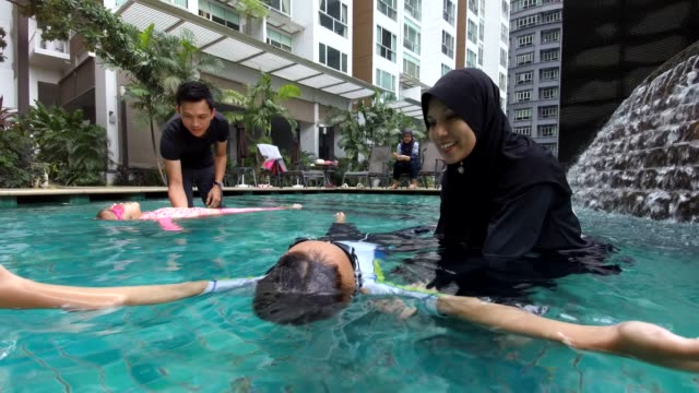 Parents helping the kids to learn to swim