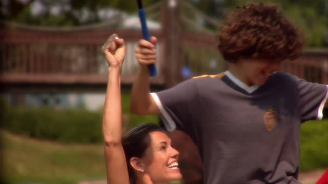 parents hoisting son onto shoulders at mini golf course and celebrating - minigolf stock-videos und b-roll-filmmaterial