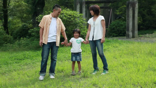 MS Parents holding hands of daughter (4-5), standing on lawn / Tokyo, Japan