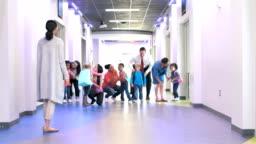 Parents in hallway drop off preschoolers with teacher