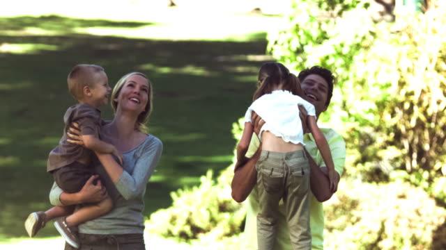 parents in slow motion holding their children - haarzopf stock-videos und b-roll-filmmaterial