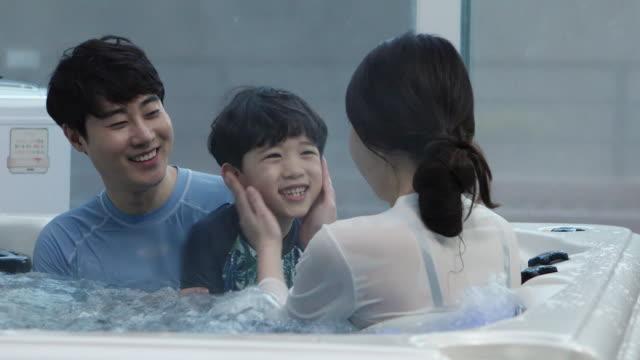 vidéos et rushes de parents in thirties and a boy enjoying lower-body bathing in winter - maillot de bain