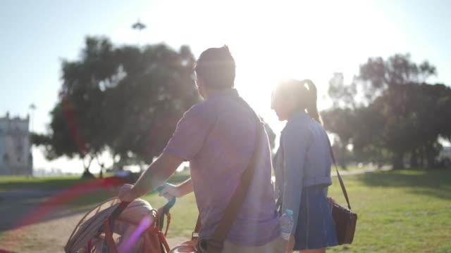 vídeos de stock, filmes e b-roll de pais na caminhada com o bebê no carrinho de criança na tarde ensolarada em lisboa - praça