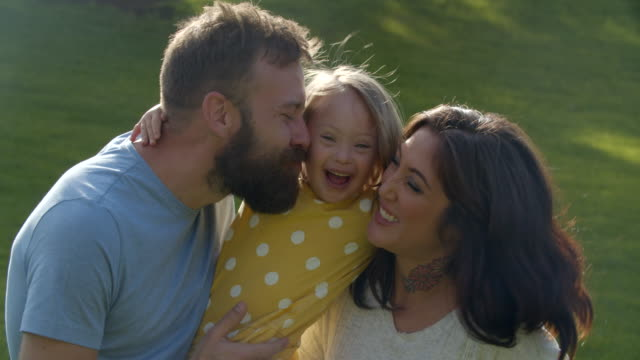 cu parents kissing their little girl with down syndrome. - braunes haar stock-videos und b-roll-filmmaterial
