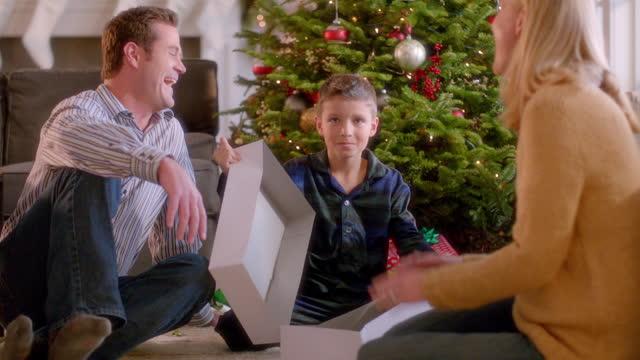 vídeos de stock e filmes b-roll de parents laugh as startled boy opens empty present in front of christmas tree - negativo tipo de imagem