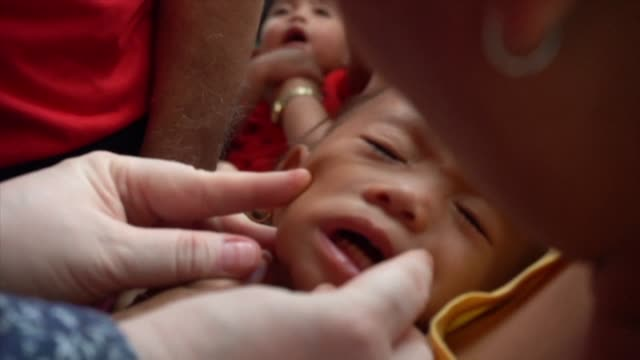 parents lined up from sunrise holding sleeping infants as the philippines launched a campaign on monday to vaccinate millions of children against... - polio stock videos & royalty-free footage