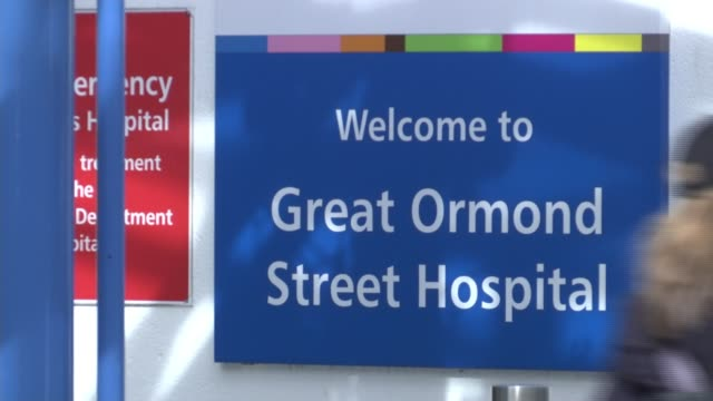 parents of baby with rare condition attempt to raise money for treatment in america; blurred shot of sign for great ormond street hospital pull focus... - バンド アメリカ点の映像素材/bロール