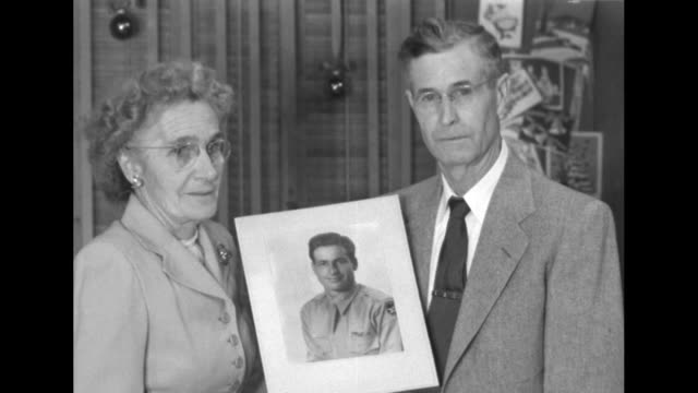 parents of pow hold his photograph and pose for camera / sot mother about son was reported missing last december, received two letters, husband... - prisoner of war stock videos & royalty-free footage