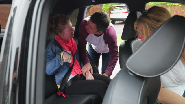 parents placing disabled daughter in the car - cerebral palsy stock videos & royalty-free footage