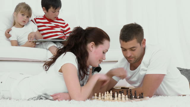 stockvideo's en b-roll-footage met ws parents playing chess on floor, son (8-9) and daughter (4-5) reading on sofa / cape town, south africa - spelletjesavond