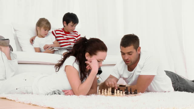 stockvideo's en b-roll-footage met ms parents playing chess on floor, son (8-9) and daughter (4-5) reading on sofa / cape town, south africa - spelletjesavond