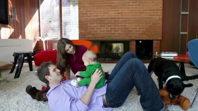 vídeos y material grabado en eventos de stock de parents playing with baby son in living room - sobre