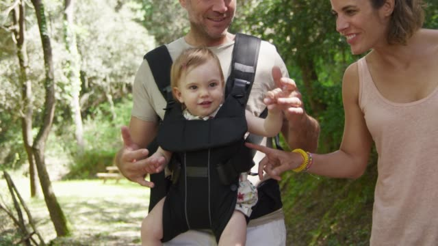 parents playing with baby while walking in forest - family with one child stock videos & royalty-free footage