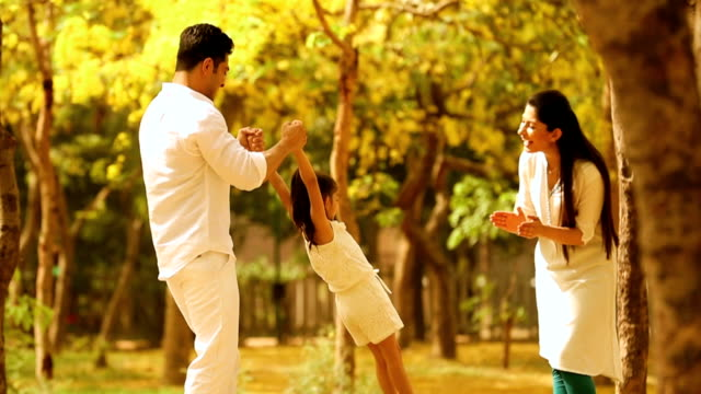 ms parents playing with daughter and enjoying in park / delhi, india - young family stock videos & royalty-free footage