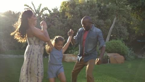 stockvideo's en b-roll-footage met parents playing with daughter in yard - twee ouders
