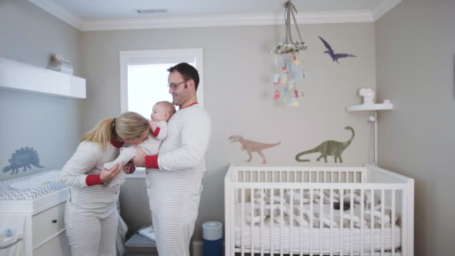 parents playing with their 6 month old  caucasian baby boy in the baby nursery - 6 11 månader bildbanksvideor och videomaterial från bakom kulisserna