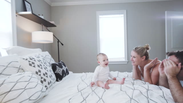 vidéos et rushes de parents playing with their 6 month old caucasian baby boy in the master bedroom - 6 11 mois