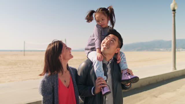 parents posing with daughter on shoulders - santa monica beach stock videos & royalty-free footage
