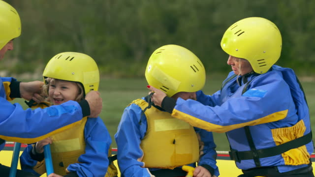 hd: parents preparing kids for rafting - flytväst bildbanksvideor och videomaterial från bakom kulisserna