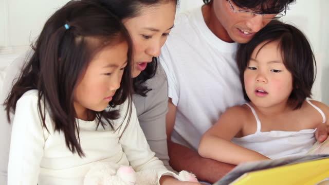 vídeos de stock, filmes e b-roll de parents reading a book to their children as they sit together - óculos de leitura