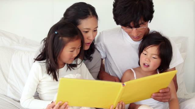 vídeos de stock, filmes e b-roll de parents reading a book to their children - óculos de leitura