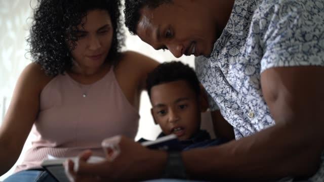 vídeos de stock, filmes e b-roll de pais que lêem um livro com o filho na cama - ler