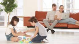 Parents relaxing on sofa while two kids playing at home